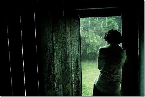 Жінка, що дивиться на дощ